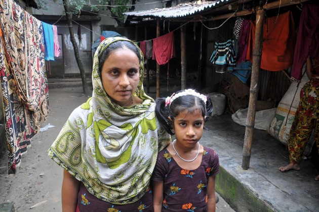 Akhter with her daughter, Riza, next to the shed they call home