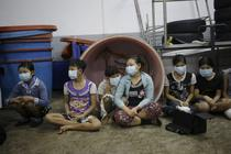 Children sit together during a raid on a shrimp shed in Samut Sakhon, Thailand