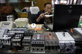 A vendor eats his meal near ABB branded products on sale at Liushi China Electronic City, a market known for its fake goods. (Photo by Ng Han/AP)