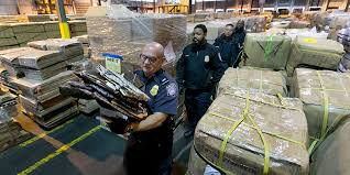 Jerome Bria, A US Customs and Border Protection officer, carries counterfeit designer bags found in a shipment at a ware house in Kearney, New Jersey (Photo by Richard Drew/AP)